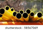 Yellow plastic pipes in sunshine - stock photo