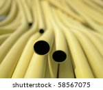 Yellow plastic pipes in a heap - stock photo