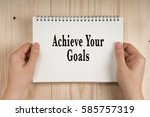Small photo of Woman holding notebook in hands with words Achieve Your Goals. Business Concept.