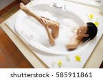 woman in bath tub washing leg ...   Shutterstock . vector #585911861