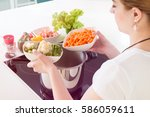 woman puts vegetables into the... | Shutterstock . vector #586059611