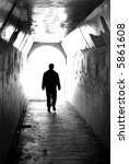 Long tunnel walkway with person at the end - stock photo