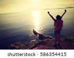 young woman hiking at sunrise... | Shutterstock . vector #586354415