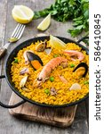 Small photo of Traditional spanish seafood paella on wooden background