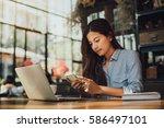 asian woman drinking coffee in... | Shutterstock . vector #586497101