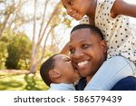 father carrying children on... | Shutterstock . vector #586579439