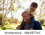 father carrying son on... | Shutterstock . vector #586587761