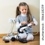 Small photo of Risky little girl dangerously playing with sockets and electricity while her parents absent