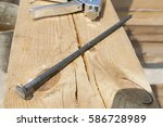 a large nail lies on a wooden... | Shutterstock . vector #586728989