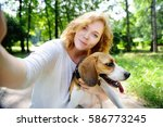 Stock photo young beautiful hipster woman making selfie photo with beagle dog using her mobile phone 586773245