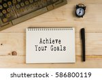 Small photo of Vintage typewriter, pen, alarm clock and notebook with words Achieve Your Goals. Business concept.
