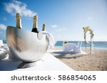 Small photo of Beautiful close-up picture of icy champagne container on the beach. Chilled ice bucket with Bright background, shining sun and sea, in Mauritius tropical island