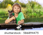 Stock photo boy and his beloved kitten playing with a boat from pier in a pond summer evening 586894475