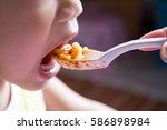 mother giving fruit sauce to... | Shutterstock . vector #586898984