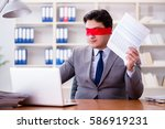 Small photo of Blindfold businessman sitting at desk in office