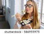 young woman savoring her sushi... | Shutterstock . vector #586955975