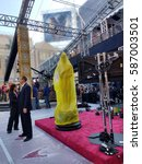Small photo of LOS ANGELES, FEB 24TH, 2017: An Oscar statue partially hidden underneath bright, yellow plastic wrap stands on a piece of red carpet during preparations for the 89th Academy Awards.