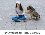 girl playing with street dog. | Shutterstock . vector #587335439