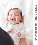 newborn baby crying in the arms ... | Shutterstock . vector #587343239