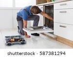 repairman examining dishwasher... | Shutterstock . vector #587381294
