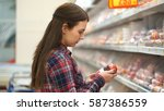 woman buys sausage in... | Shutterstock . vector #587386559