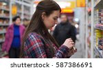 woman buys canned food in... | Shutterstock . vector #587386691