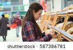 woman buys bread in supermarket ... | Shutterstock . vector #587386781