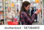 woman buys juice in supermarket ... | Shutterstock . vector #587386805