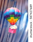 Small photo of Colorful aerostat or air balloon toy with a gift box. Likely for birthday, holiday, or wedding.