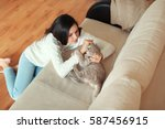 Stock photo young woman playing with cute cat at home 587456915