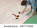 man installing new wooden... | Shutterstock . vector #587773385