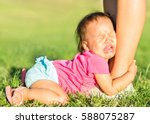 crying baby girl holding onto... | Shutterstock . vector #588075287