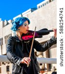 Small photo of Woman perform music on violin in park outdoor. Girl performing jazz on city street . Spring outside with blue hairstyle background.