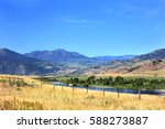 Yellowstone River runs through mountains and golden field in Montana.