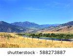 Yellowstone River runs through mountains and golden field in Montana.