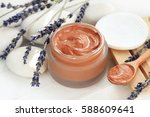 Cosmetic red clay mask mixed in jar, dried lavender flower twigs on white stones