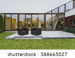 Small photo of Ascetic villa patio with rattan chairs and grey floor