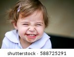 Stock photo lovely little girl making funny face after eating chocolate 588725291