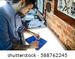 worker of tattoo salon drawing... | Shutterstock . vector #588762245