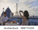 Romantic couple using technology digital tablet smart phone taking photo hotel breakfast terrace honeymoon Eiffel Tower Paris destination