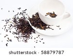black tea scattered around the cup and on the dish - stock photo