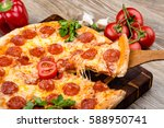 photo of a hot pizza on wooden... | Shutterstock . vector #588950741