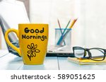 Small photo of Good morning message on coffee cup at workplace background