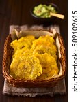 Small photo of Patacon or toston fried and flattened pieces of green plantain, traditional snack or accompaniment in the Caribbean, guacamole in back, photographed with natural light (Selective Focus on first slice)
