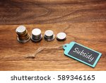 Small photo of coins stacked and subsidy written on the blackboard.
