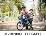 little sibling boy riding bike... | Shutterstock . vector #589416569