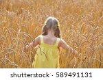 beautiful girl among wheat ears | Shutterstock . vector #589491131