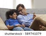 smiling father and son sitting... | Shutterstock . vector #589741079