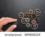 hand placing a gear into other... | Shutterstock . vector #589808339
