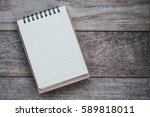 blank notepad on a wooden table. | Shutterstock . vector #589818011